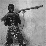 Man with Gun, Jacmel, Haiti , 2004. Courtesy of Phyllis Galembo/Steven Kash...