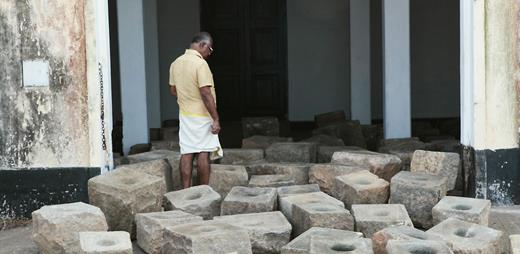 """Stopover, an installation of spice grindstones by Indian artist Sheela Gowda and Christoph Storz, at the dockside of Aspinwall House. The traditional grindstones were used domestically as part of the traditional preparation of spices but are now redundant, as housewives have moved to electrical grinders, leaving a legacy of abandoned utensils as a reminder of change and of the """"daily grind"""" and hard manual labor of everyday life for the majority of Indians. The grindstones become significant memorials in Fort Kochi, a key historic spice-trading port and nexus of global trade. Photograph courtesy of the author 2012"""