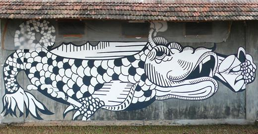 Dragonfish, a painted wall mural by Indian artist Anpu Varkey, becomes a marker of India's absorption of contemporary, non-Indian art forms. It has a considered placement on the sea-facing wall of the eighteenth-century dockside store Pepper House, making the ancient fish motif contemporary with cigarettes and beer, and it is visible to boats and the local fishing community. While the graffiti-inspired mural is a new format for the streets of Fort Kochi, it is one that is growing in the metropolitan cities of Mumbai and Delhi, where the artist is based. While the Kochi-Muziris Biennale promotes the fact that it is bringing new and radical art forms to an Indian art event, in reality these works are neutered of much of the subversiveness of the street graffiti from which they are derived. Photograph courtesy of the author 2012