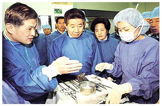 "President Roh Moo-hyun (center) visiting Hwang's lab (December 10, 2003). Roh was so deeply impressed by Hwang's presentation (he used the word ""electrified"") that he promised firm support to Hwang's future research, while the questions about ethical issues already were raised then"