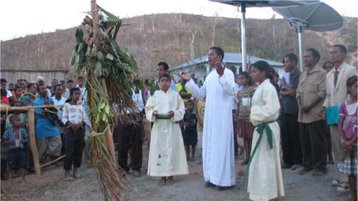 In a conflation of animism and Catholicism, the priest stands before the tara bandu cross and gives his blessing.