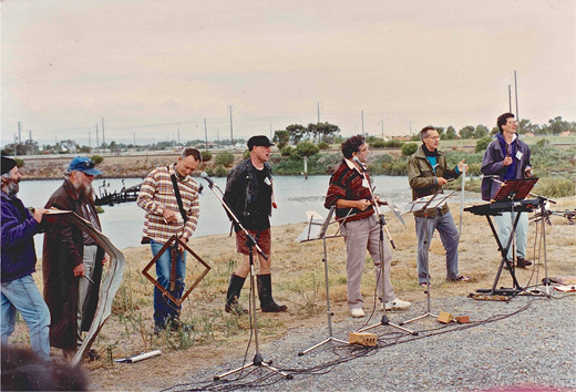 "The Junk Naturals perform ""Junk: A Natural Part of Life"" at Ethelton, 13 April 1996. L to R: Tony Bazeley, Roger Laws, Mike Watters, Rod Boucher, Chester Schultz, Ian Farr, Anthony Pak Poy. Image courtesy Geoff Willsmore."