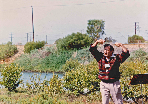 "Chester Schultz, standing in the mouth of Mangrove Creek, Ethelton, conducts the ""River Chant"" on 13 April 1996. Image courtesy Geoff Boyce."