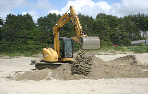 The excavator fills the hole back in with sand. Photo: Oregon Parks and Recreation Department.