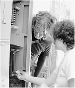 Volunteer cleaning a transmitter while engineer looks <b>on</b>   Figure 5. Volunt...