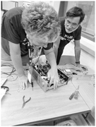 Fixit Clinic coaches S. and C. collaboratively inspect a faulty switch <b>on</b> a...