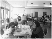 The sewing table: Fixit Clinic coach E. helps <b>women</b> clean the inside of the...