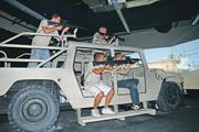 AEC visitors play <b>on</b> the Humvee truck simulator. Source: Department of Defe...