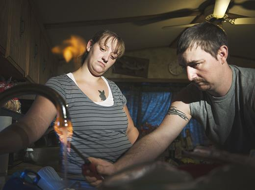 Jodie Simons and Jason Lamphere of Monroeton, PA, demonstrate how their tap water ignites due to high concentrations of methane. Photograph by Nina Berman