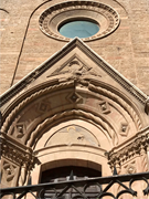 Defaced tympanum of seated Virgin Mary above <b>one</b> of the entrances to the It...