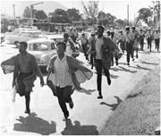 The Police chasing University of the West Indies students who were demonstr...