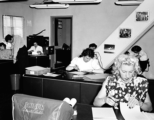 """Human computers in the NACA High Speed Flight Station """"Computer Room"""" transcribing raw data from rolls of celluloid film and strips of oscillograph paper and reducing it to standard engineering units with slide rules and electric calculators. Seen here, left side, front to back, Mary """"Tut"""" Hedgepeth, John Mayer, and Emily Stephens. Right side, front to back, Lilly Ann Bajus, Roxanah Yancey, Gertrude """"Trudy"""" Valentine (behind Yancey), and Ilene Alexander. Dryden Flight Research Center Facilities, 1949, NACA (NASA). Photograph courtesy of NASA"""