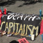 Votive candles line an altar to the death of capitalism at Occupy Oakland o...
