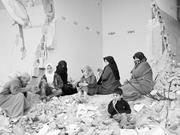 Creative Commons/rafahkid  Palestinians in Jabalia sit amid rubble in the a...