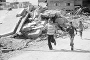 Creative Commons/gloucester2gaza  Children run past bombed-out buildings in...