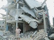 A <b>man</b> stands in front of his destroyed home in Beit Hanoun, a part of Gaza ...
