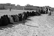 Alima, a three-year-old Afghan girl, lines up with <b>other</b> IDPs to receive wi...