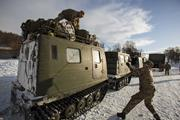 Marines <b>secure</b> gear atop Swedish BV tracked vehicles—the only motorized tra...