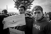 """Two men in Idomeni refugee <b>camp</b> hold a sign that reads, """"If you don't open ..."""
